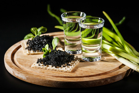 Vodka and black caviar on black background Imagens
