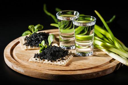 Vodka and black caviar on black background Archivio Fotografico