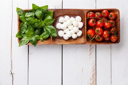 tomate cherry: Albahaca verde, mozzarella blanco, tomates rojos - los colores de la bandera italiana Foto de archivo