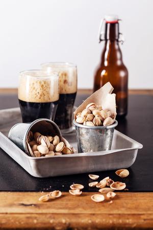 schwarzbier: Dunkles Bier und gesalzene Pistazien Lizenzfreie Bilder