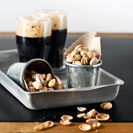 beerglass: Dark beer and pistachios at textured table
