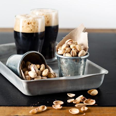 schwarzbier: Dunkles Bier und Pistazien auf strukturierte Tabelle Lizenzfreie Bilder