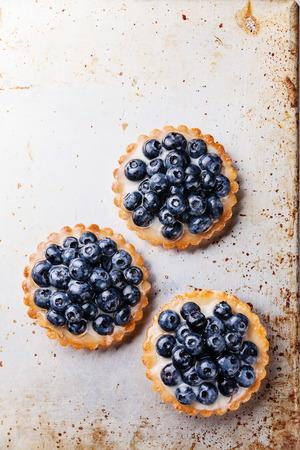 Three blueberry tarts on rusty surface texture