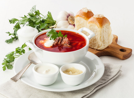 Sour cream: Red borsch with traditional Ukrainian bread pampushki  Stock Photo