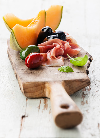 Prosciutto ham, Slices of melon cantaloupe and Olives on cutting board
