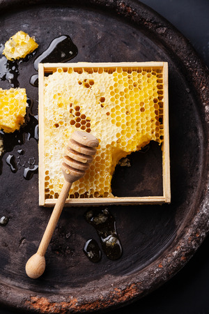 honey comb: Honeycomb with wooden honey dipper on black textured background Stock Photo