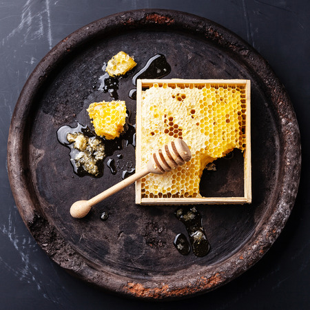 black textured background: Honeycomb with wooden honey dipper on black textured background Stock Photo