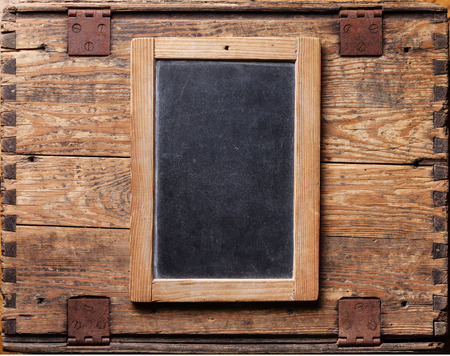 Vintage slate chalk board on wooden background Imagens