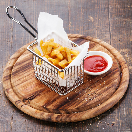 French fries in baskets for serving on wooden background