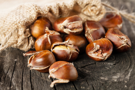 Roasted chestnuts in burlap bag on wooden background