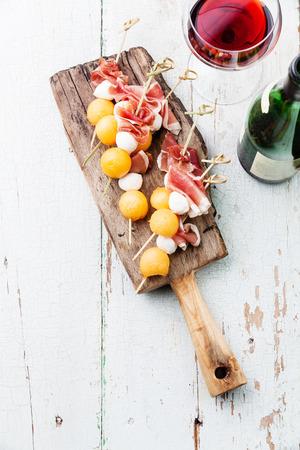 Mozzarella, prosciutto, melon canapes and wine on textured background