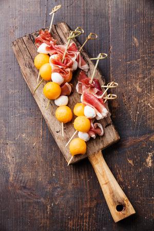 Mozzarella, prosciutto, melon canapes on dark wooden background Reklamní fotografie