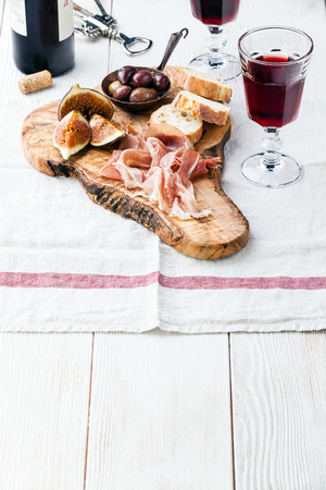 Prosciutto ham, Olives and red Wine on olive wood cutting board Imagens