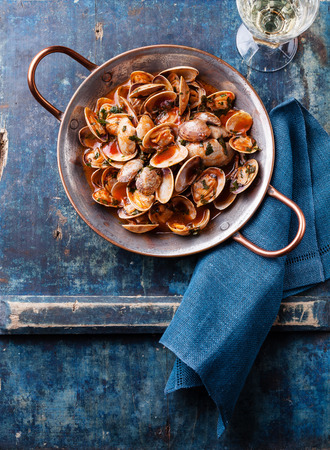 Shells vongole with parsley and tomato sauce and wine on blue background Imagens