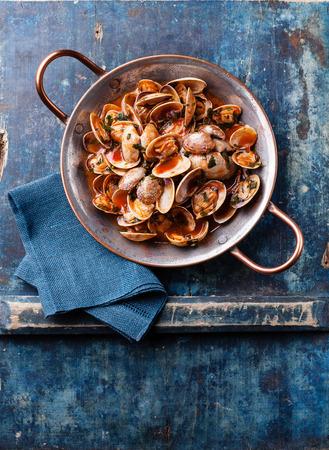 Shells vongole with parsley and tomato sauce on blue background Reklamní fotografie