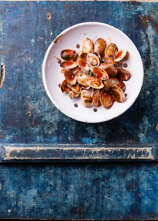 Conchiglie vongole con prezzemolo e salsa di pomodoro in epoca colino in ceramica su sfondo blu Archivio Fotografico - 31038553