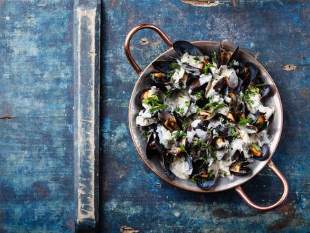 파란색 배경에 구리 요리 접시에 홍합과 도르 블루 소스