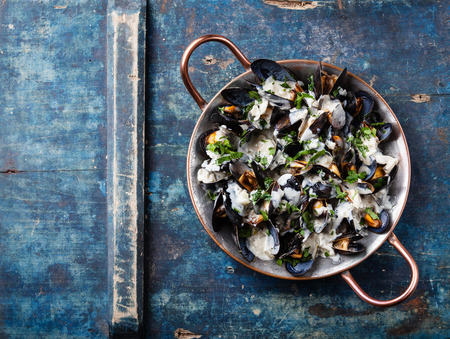 Mussels and Dor Blue sauce in copper cooking dish on blue background