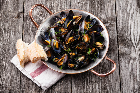 Mussels in copper cooking dish and French Baguette on dark wooden background