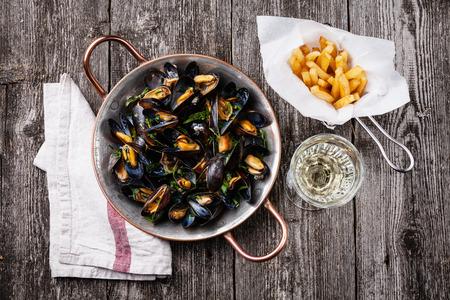 홍합, 감자 튀김 및 어두운 나무 배경에 와인 스톡 콘텐츠
