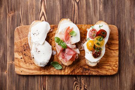 Three bruschettas with mozzarella cheese, ham and roasted tomatoes on ciabatta bread on wooden background