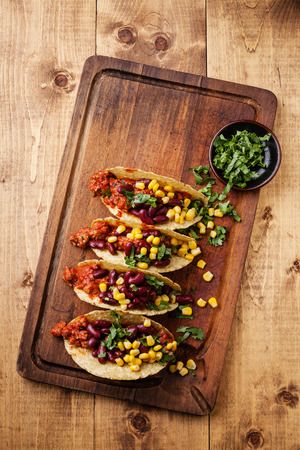 Tacos with ground beef, corn and red beans on wooden table Banco de Imagens