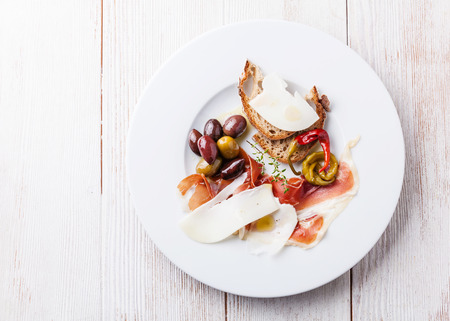 Appetizer with ham, cheese and olives on white plate