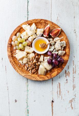 올리브 나무 접시에 치즈의 다양 한 종류의 치즈 플레이트의 구색 스톡 콘텐츠
