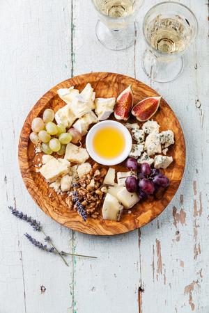 치즈 플레이트 및 와인 올리브 나무 접시에 치즈의 다양 한 종류의 구색 스톡 콘텐츠