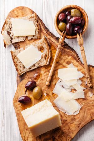 Panini con parmigiano e olive su un tagliere di legno d'ulivo Archivio Fotografico - 31361497