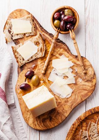 Panini con parmigiano e olive su un tagliere di legno d'ulivo Archivio Fotografico - 31361498