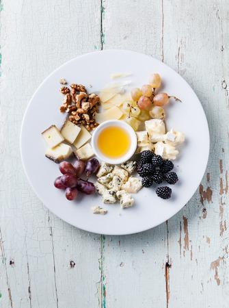 치즈 플레이트 다양한 종류의 치즈와 꿀 하얀 접시에 구색