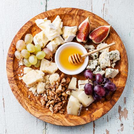 치즈 플레이트 올리브 나무 접시에 치즈의 다양한 종류의 구색 스톡 콘텐츠