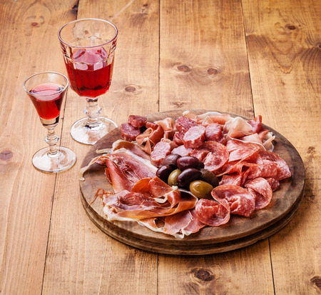 salami: Plato de carne fría y el vino en el fondo de madera