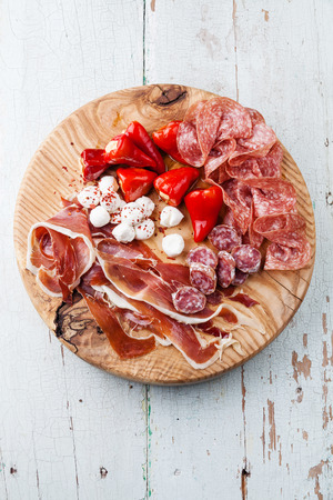 Cold meat plate and sweet peppers on wooden background