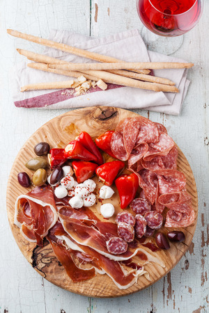 Cold meat plate and grissini bread sticks on wooden background  写真素材