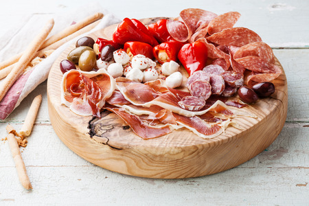 Cold meat plate and grissini bread sticks on wooden background  Stockfoto