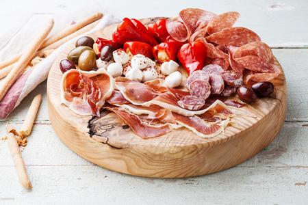 frio: Plato de carne fr�a y pan bastones grisines sobre fondo de madera