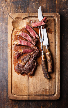 dark meat: Medium rare Beef steak Ribeye with knife and fork for meat on cutting board on dark wooden background