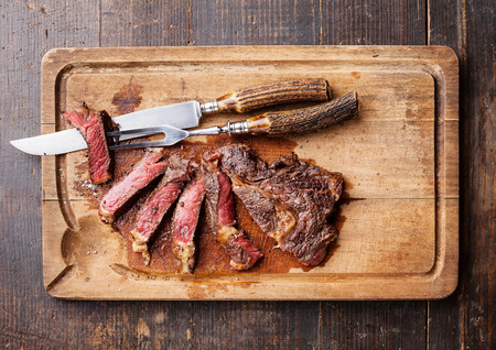 dark meat: Medium rare grilled Beef steak Ribeye with knife and fork for meat on cutting board on dark wooden background Stock Photo
