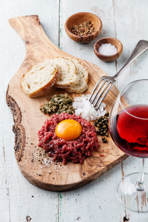 Beef tartare with capers and fresh onion on olive wood board with wine