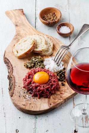 alcaparras: Tartar de ternera con alcaparras y cebolla fresca sobre tablero de madera de olivo con vino