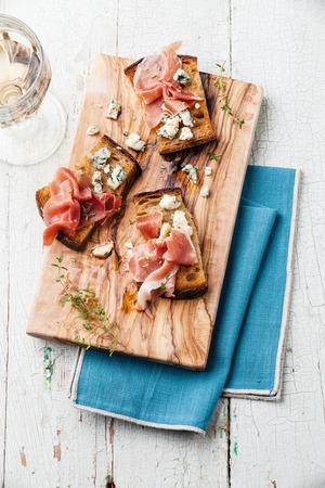 Bruschette con formaggio blu e prosciutto in crosta di pane alla griglia su sfondo blu di legno Archivio Fotografico - 31476935
