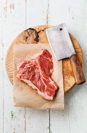 Raw fresh meat T-Bone Steak and meat cleaver on cutting board on blue background