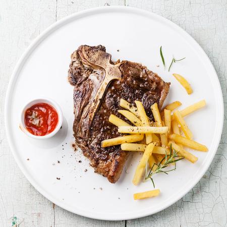 푸른 나무 배경에 흰색 접시에 소금에 절인 감자 튀김 T-뼈 스테이크 스톡 콘텐츠 - 31476941