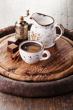 핫 초콜릿은 어두운 나무 배경에 계피를 뿌렸다.