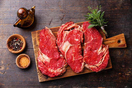 Raw fresh meat Ribeye steak entrecote and seasoning on dark wooden background 写真素材