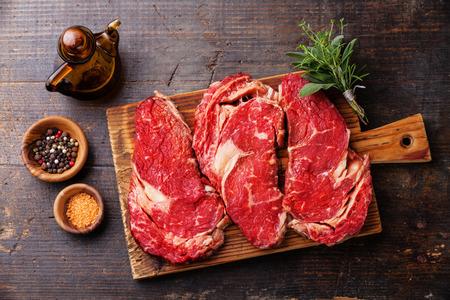 어두운 나무 배경에 원시 신선한 고기 RIBEYE 스테이크 entrecote 및 조미료