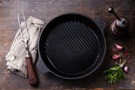 Black iron empty grill pan and meat fork on wooden texture background