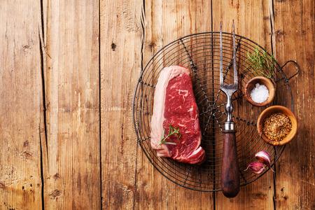Carne fresca cruda di manzo sudamericano premio New York bistecca sul filo rack di raffreddamento su sfondo di legno Archivio Fotografico - 33126845